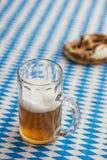 Oktoberfest: Ciambellina salata e birra sulla tovaglia bavarese Immagini Stock