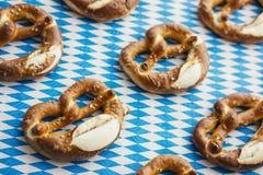 Oktoberfest: Ciambelline salate sulla tovaglia bavarese Fotografie Stock Libere da Diritti