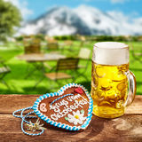 Oktoberfest concept with ginger heart and beer. Oktoberfest concept with a ginger heart with decorative icing and a glass tankard of beer or lager outdoors on a royalty free stock photography