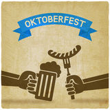 Oktoberfest concept. Hand with beer mug and sausage old background Stock Photography