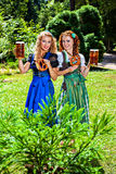 Oktoberfest - Dirndl, Pretzel and Beer. Two girls in dirndl dress holding Oktoberfest beer stein and pretzel royalty free stock photos
