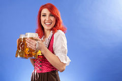 Oktoberfest female smiling with beer. Photo of a beautiful female waitress wearing traditional dirndl and holding two mass beer steins Stock Photo