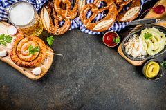 Oktoberfest food concept. Oktoberfest food menu, bavarian sausages with pretzels, mashed potato, sauerkraut, beer bottle and mug, dark rusty background copy stock photography