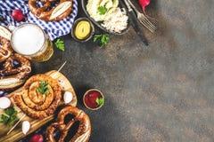 Oktoberfest food concept. Oktoberfest food menu, bavarian sausages with pretzels, mashed potato, sauerkraut, beer bottle and mug, dark rusty background copy royalty free stock image