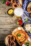 Oktoberfest food concept. Oktoberfest food menu, bavarian sausages with pretzels, mashed potato, sauerkraut, beer bottle and mug old rustic wooden background royalty free stock photos