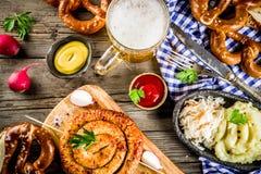 Oktoberfest food concept. Oktoberfest food menu, bavarian sausages with pretzels, mashed potato, sauerkraut, beer bottle and mug old rustic wooden background royalty free stock images