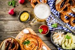 Oktoberfest food concept. Oktoberfest food menu, bavarian sausages with pretzels, mashed potato, sauerkraut, beer bottle and mug old rustic wooden background stock image