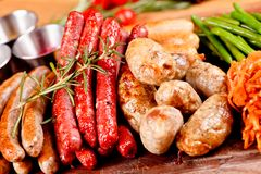 Oktoberfest food menu. Assorted grilled sausages, sauerkraut, green beans on wooden cutting board. Close up royalty free stock photo