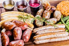 Oktoberfest food menu. Assorted grilled sausages, sauerkraut, green beans on wooden cutting board. Close up royalty free stock images