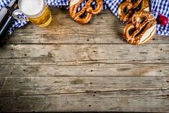Oktoberfest food concept. Oktoberfest food menu, bavarian pretzels with beer bottle mug on old rustic wooden background, copy space above royalty free stock image
