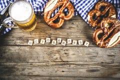 Oktoberfest food concept. Oktoberfest food menu, bavarian pretzels with beer bottle mug on old rustic wooden background, copy space above stock images