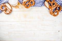 Oktoberfest food concept. Oktoberfest food menu, bavarian pretzels with beer bottle mug, white wooden background copy space top view royalty free stock photo