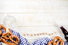 Oktoberfest food concept. Oktoberfest food menu, bavarian pretzels with beer bottle mug, white wooden background copy space top view stock image