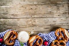 Oktoberfest food concept. Oktoberfest food menu, bavarian pretzels with beer mug, old rustic wooden background, copy space above stock photography
