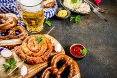 Oktoberfest food concept. Oktoberfest food menu, bavarian sausages with pretzels, mashed potato, sauerkraut, beer bottle and mug, dark rusty background copy royalty free stock photography