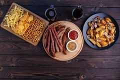 Oktoberfest food, pub concept. Two mugs of dark beer with great. Assortment of appetizing snacks: sausages, french fries, baked potatoes, pretzel crackers stock photography