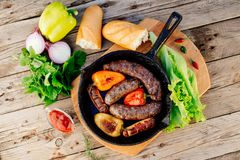 Oktoberfest. Fried lamb sausages and sweet peppers on a cast-iron frying pan stock photography