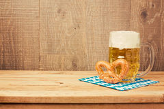 Oktoberfest german beer festival background with beer glass and pretzel on wooden table royalty free stock photo