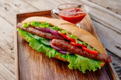 Oktoberfest. German hot dog with grilled sausages, onions and vegetables. French roll with grilled sausages from lamb royalty free stock photos