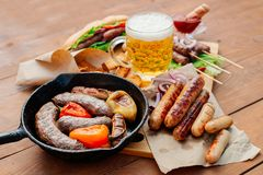 Oktoberfest. A glass of beer on a wooden table, around a selection of different sausages cooked on the grill. Sausages and pepper on a cast-iron frying pan stock images