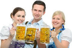 Oktoberfest. Group of young people in traditional bavarian tracht holding Oktoberfest beer steins royalty free stock photos