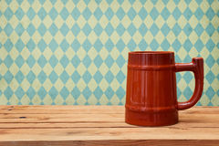 Oktoberfest holiday. Beer on wooden table over retro wallpaper with bavarian flag pattern Stock Images