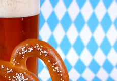 Oktoberfest image. A mug of dark beer with a giant pretzel in front of a Bavarian blue and white diamond background with copy space stock images