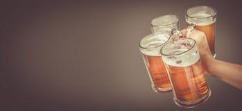 Oktoberfest-Konzept - übergeben Sie das Halten von Gläsern mit Bier stockfotografie