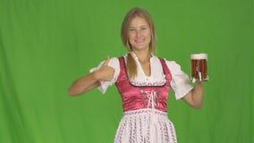 Oktoberfest-Mädchen im nationalen Kostüm von Bayern hält ein Glas Bier und lächelt, es zeigend und zeigt Klasse, Grün stock video