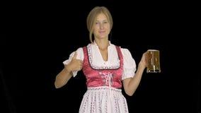 Oktoberfest-Mädchen im nationalen Kostüm von Bayern hält ein Glas Bier und lächelt, es zeigend und zeigt Klasse, Schwarzes stock video