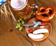Oktoberfest-Menü mit Bier, weißer Wurst, Brezel und Rettich Lizenzfreies Stockfoto