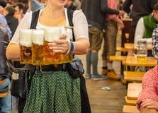 Oktoberfest, Munich, Alemanha Garçom com o traje tradicional que guarda cervejas fotografia de stock
