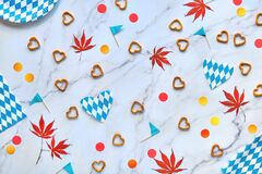 Free Oktoberfest Party Background With Red And Yellow Confetti And Maple Leaves. Flat Lay On Marble Table. Bavarian Blue White Royalty Free Stock Photos - 194806698