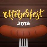 Oktoberfest 2018 Saucisse bavaroise sur la fourchette, le fond en bois et le lettrage 2018 à la mode d'Oktoberfest Photographie stock libre de droits