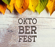 Oktoberfest sign and colorful autumn leaves. White wooden backgr. Oktoberfest sign and colorful autumn leaves. Studio shot on white wooden background Stock Photos
