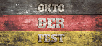 Oktoberfest sign, German flag on old wood plank background. Oktoberfest sign, German flag, red, yellow and black stripes, painted on aged wall. Studio shot stock photography