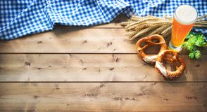 Oktoberfest tło z Bawarską flaga, piwnym szkłem i pretze, zdjęcia stock