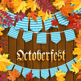 Oktoberfest .Traditional German autumn festival of beer background.TGarlands and flags with traditional decor on wooden. Background with frame of autumn leaves Stock Photo