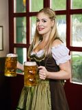 Oktoberfest waitress serving beer. Photo of a beautiful female waitress wearing traditional dirndl and holding huge beers in a pub Stock Photos