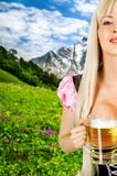Oktoberfest woman with big breast Holds beer mug. Young beautiful blond oktoberfest woman with big neckline on female breast Holds two mugs with light beer Royalty Free Stock Image