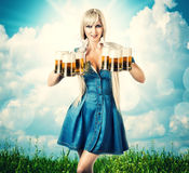 Oktoberfest woman with six beer mugs. Young sexy oktoberfest woman wearing a dirndl holding six beer mugs. outdoor background with grass and sky Stock Photo