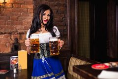 Oktoberfest woman wearing a traditional Bavarian dress dirndl posing with a beer mug at bar. Woman wearing a traditional Bavarian dress dirndl posing with a beer stock images