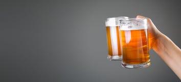 Oktoberfestconcept - de glazen van de handholding met bier stock foto's