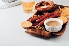 Oktoberfestvoedsel, smakelijke die biersnacks voor groot bedrijf worden geplaatst Geroosterde worsten, spaanders, pretzel stock foto