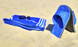 Okulary przeciwsłoneczni, błękitny ręcznik i kapcie na piaskowatej plaży, Fotografia Royalty Free