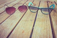 Okulary przeciwsłoneczni fasonują na drewno stole, brown tło Obrazy Royalty Free