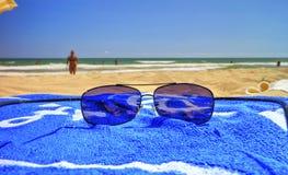 Okulary przeciwsłoneczni i błękitny ręcznik na piaskowatej plaży Zdjęcia Stock