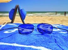 Okulary przeciwsłoneczni i błękitny ręcznik na piaskowatej plaży Zdjęcie Stock