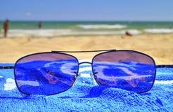 Okulary przeciwsłoneczni i błękitny ręcznik na piaskowatej plaży Obrazy Stock