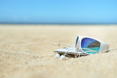 Okulary przeciwsłoneczni i telefon na plaży Obraz Royalty Free